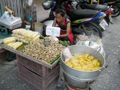 a street vendor sells corn on the cob, steamed peanuts and sweet potato