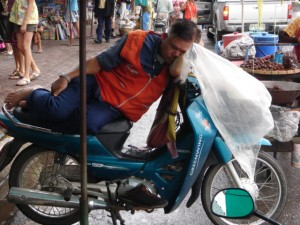 Motorcycle Taxi Driver sleeping on his Bike in Mae Sai