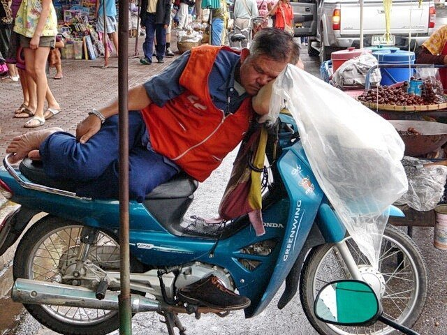 Thai man sleeping on a scooter