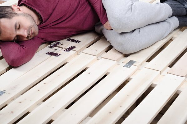man sleeping on wooden bed